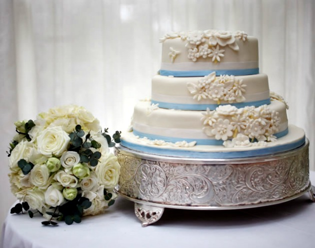 JK Photography Blue Rimmed White Wedding Cake with Silver Platform and Cream Bouquet