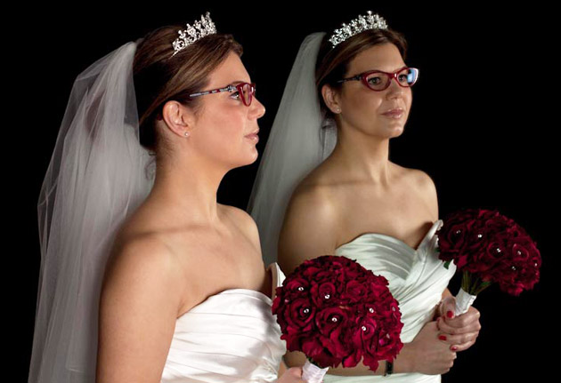 Bride with glasses holding red bouquet