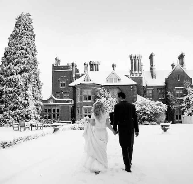 Bride and groom in the snow outside beautiful wedding venue