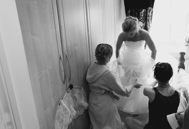 Bridesmaids helping bride in to her dress