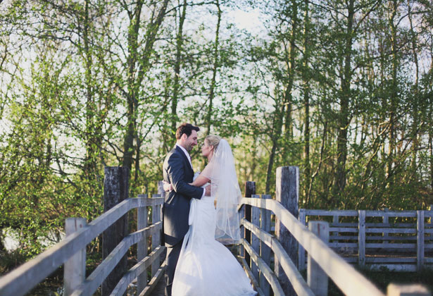 The bride and groom on a bridge by Sansom Photography