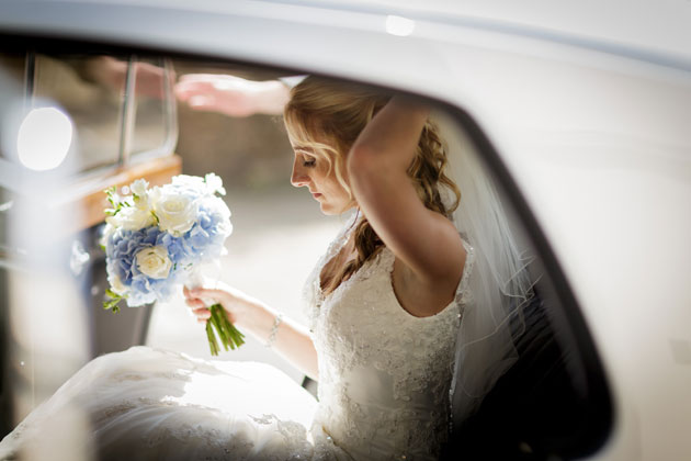 The bride in a silver vintage wedding car