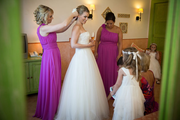 Bridesmiad adding a flower to the brides hair