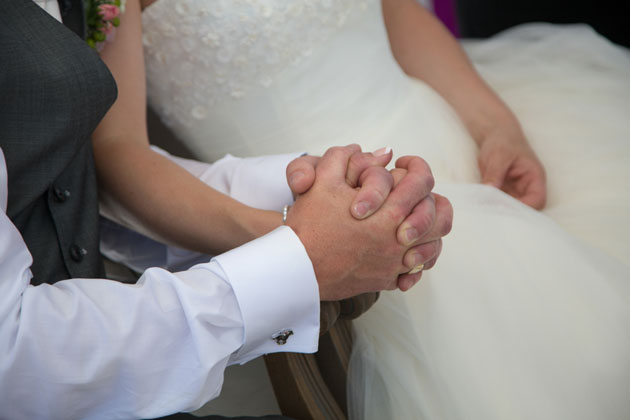 The bride and groom holding hands during the ceremony