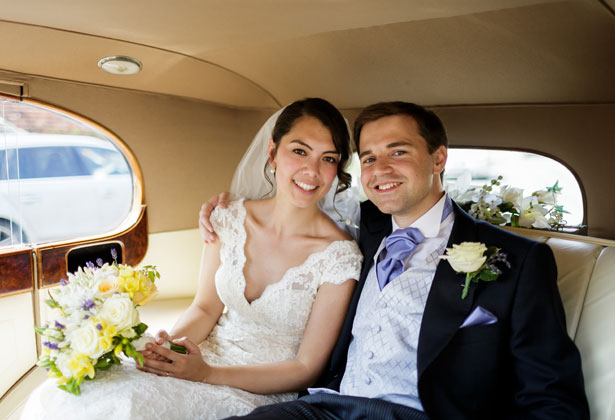 Bride and groom leaving the church in a vintage car