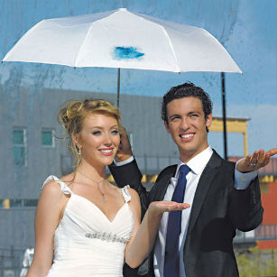 Bride and groom under umbrella