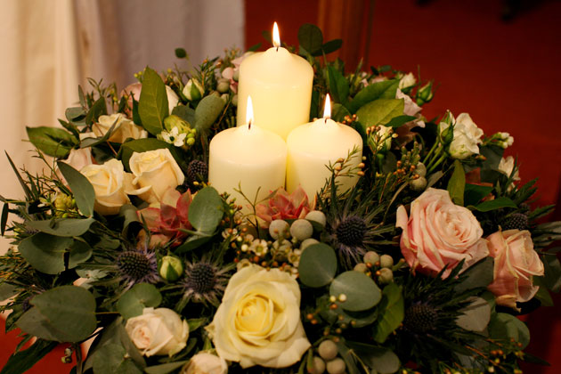 Winter inspired flower arrangement with roses, candles and thistles