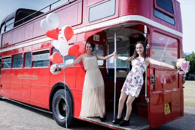 Bridesmaids with heart shaped balloons on the red bus