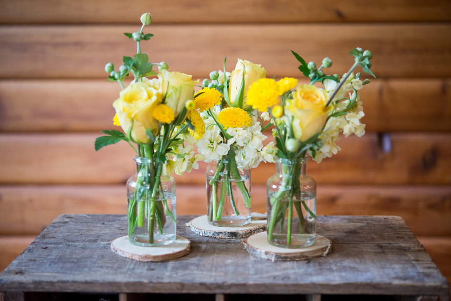 Glass Bottles and Flowers Rustic Decor | Confetti.co.uk