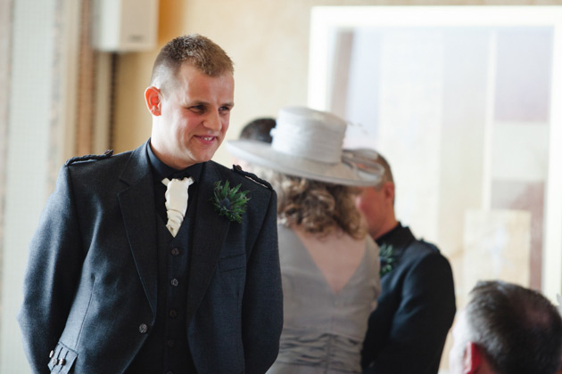 The groom in a grey kilt with a thistle button hole