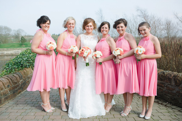 Bridesmaids in coral pink knee length dresses with a draped halter neck