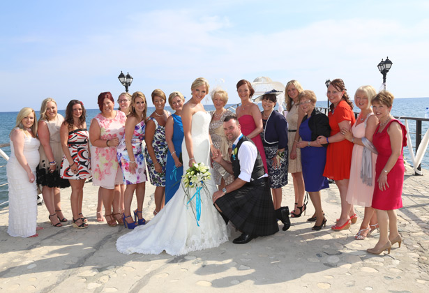 The happy couple with their family and friends on the pier