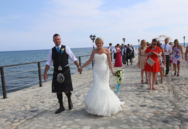 The bride and groom holding hands on the pier
