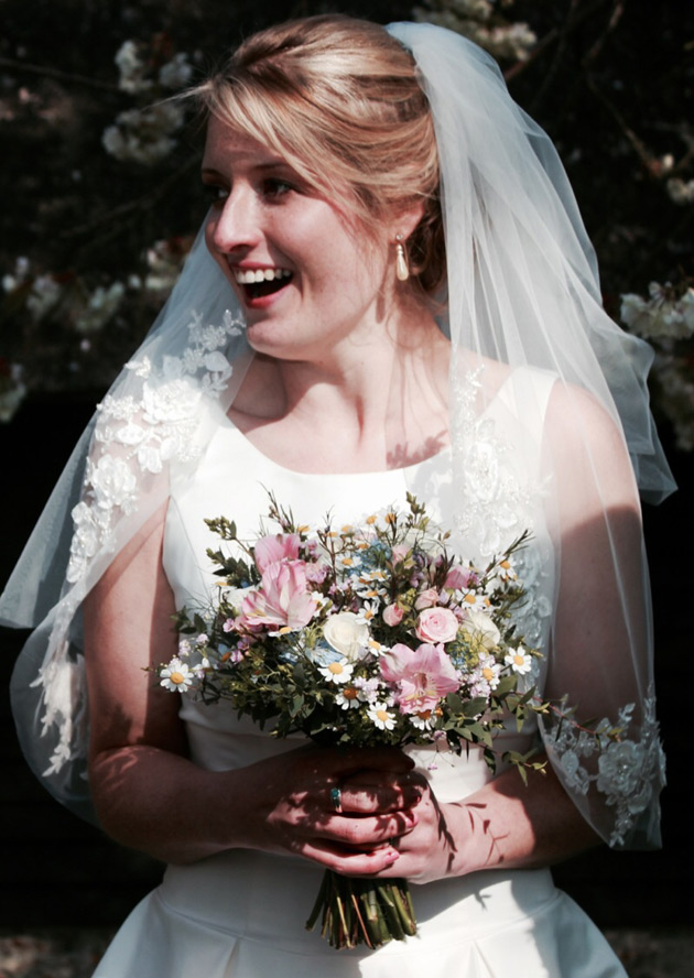 Bride in her white lace gown and vintage bouquet