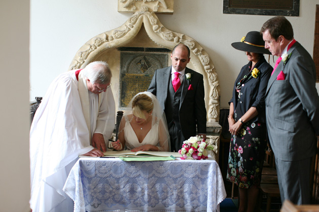The newlyweds signing the register| Confetti.co.uk