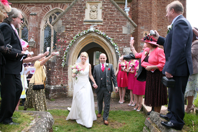 Wedding guests throwing confetti over the newlyweds after the church ceremony   Confetti.co.uk