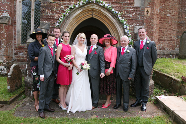 The bride and groom and families pose for a photo outside the wedding venue | Confetti.co.uk