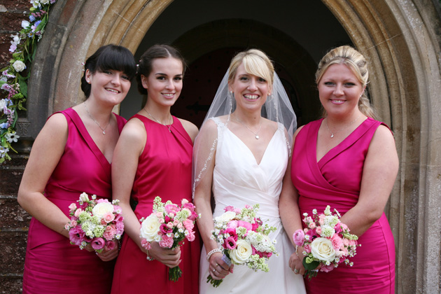 The bride in her blush pink wedding dress and bridesmaids in their hot pink sleeveless dresses | Confetti.co.uk