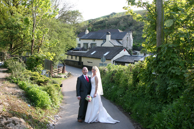 The bride and groom pose in a quaint English village on their wedding day | Ava Images | Confetti.co.uk