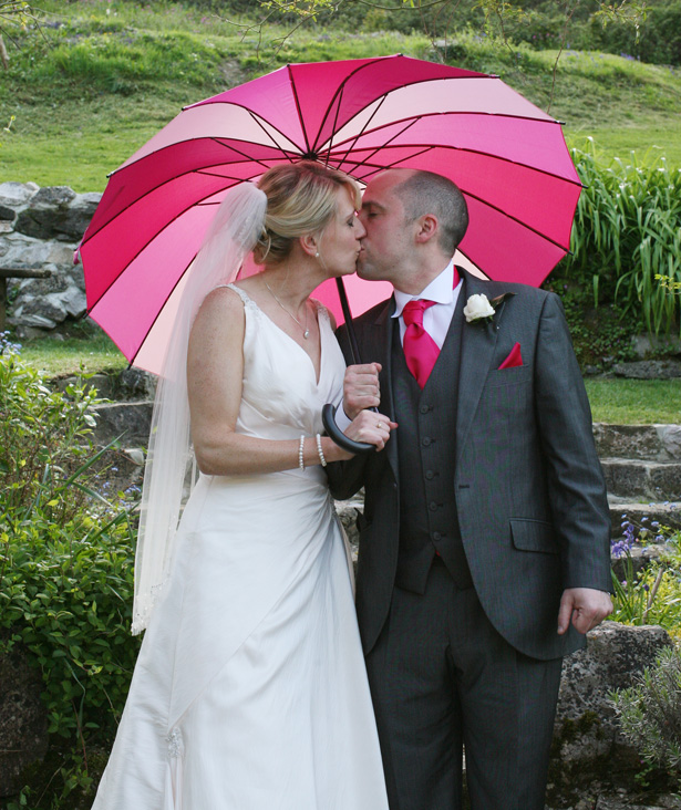The bride and groom sneek a kiss under a pink umbrella | Ava Images | Confetti.co.uk