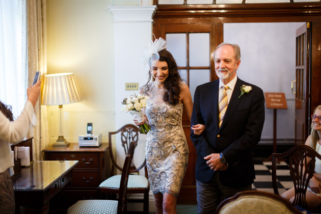 Bride in a short detailed wedding dress with white fascinator walking down the aisle with her father   Confetti.co.uk