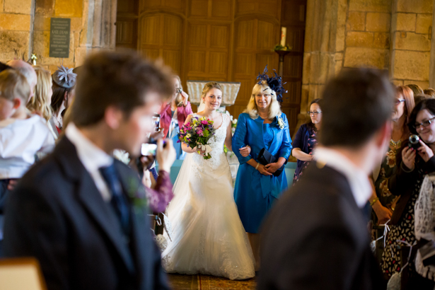 Bride walking down the aisle with her mum | Confetti.co.uk