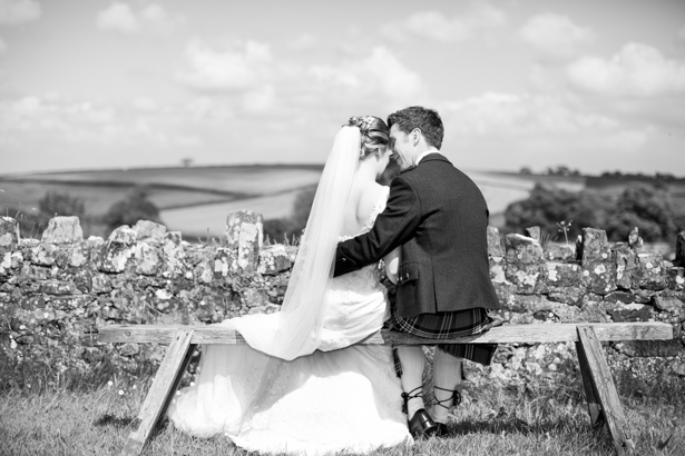 Bride and groom sitting on the bench | Confetti.co.uk