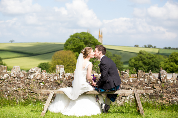The newlyweds kissing on the bench | Confetti.co.uk