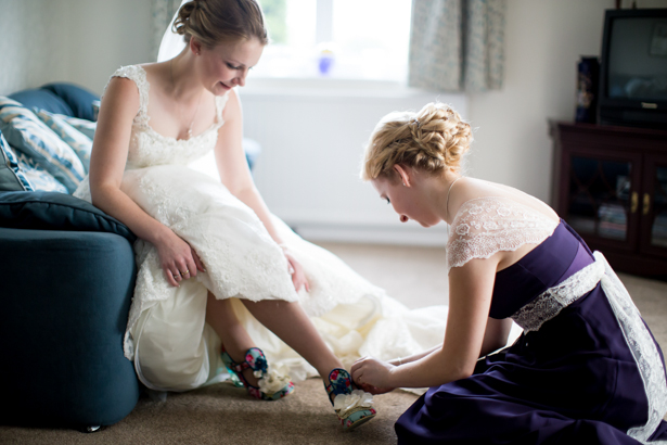 Bridesmaid helping the bride tie her shoe | Wedding moment | Confetti.co.uk