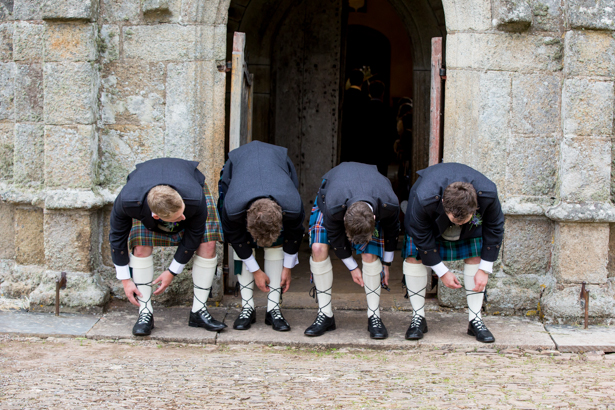 Groom and groomsmen adjusting their socks | Confetti.co.uk