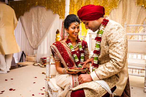 Bride and groom in the mandap enjoying the ceremony | Traditional Hindu wedding customs | Confetti.co.uk