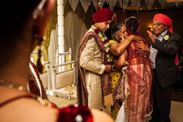 Bride embracing her family members after the Hindu ceremony | Traditional Hindu wedding customs | Confetti.co.uk