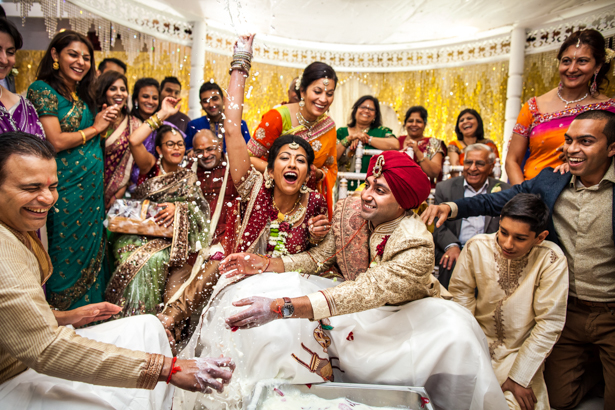 Bride and groom playing a traditional game of hiding their rings | Traditional Hindu wedding customs | Confetti.co.uk