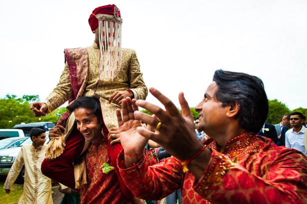 Indian groom in traditional gold and red sherwani arriving at the ceremony with the baraat| Confetti.co.uk