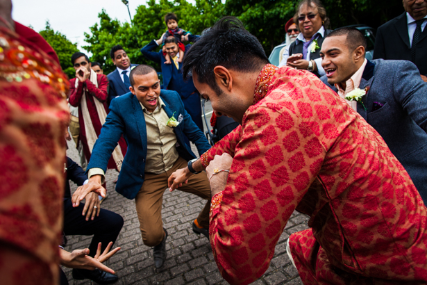 Wedding guests, in traditional Indian wedding outfits, dancing as they make their way to the Hindu wedding ceremony | Confetti.co.uk