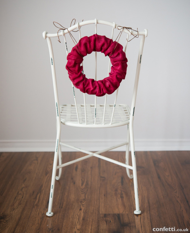 Bright red wreath as a wedding chair decoration | Confetti.co.uk