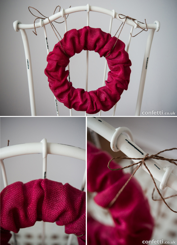 Cranberry red burlap wreath tied with twine to a chair back | Confetti.co.uk