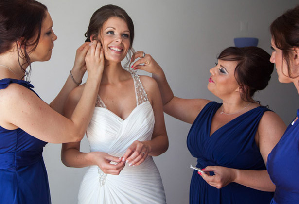 How to Choose Your Bridesmaids | Bridesmaids in royal blue dresses helping the bride with her accessories | Confetti.co.uk