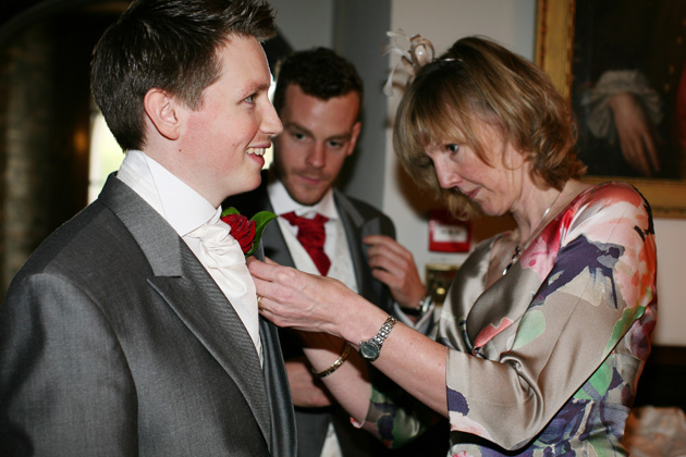 Mother of the Groom Wedding Duties | Image courtesy of AVA Images | Mother of the groom pinning the grooms red rose button hole | Confetti.co.uk