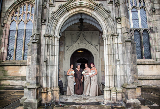 Bridesmaids in long brown strapless dress outside the St. Michael and all Angels' church in Ashton | Becki and Rob's Real Wedding By Jenny Martin Photography | Confetti.co.uk