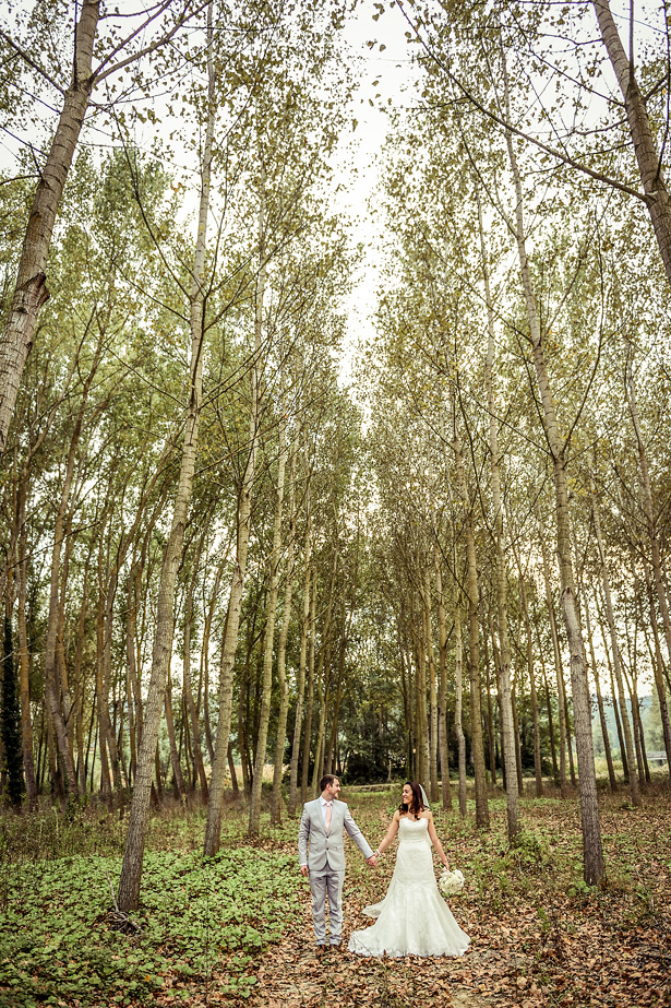 Official wedding shot in the forest | Bride and groom holding hands in the forest | Morgan and James Real Wedding By Infinity Weddings | Confetti.co.uk