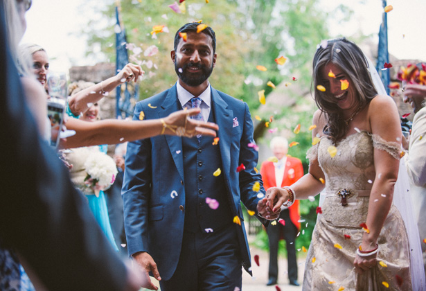 The newlyweds | Guests throwing colourful rose petal confetti over the bride and groom as they leave the church | Francesca & Arun's Fusion Real Wedding | Confetti.co.uk