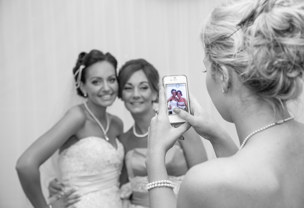 Wedding guest take a picture of the bride with her bridesmaid   Becki and Rob's Real Wedding By Jenny Martin Photography   Confetti.co.uk