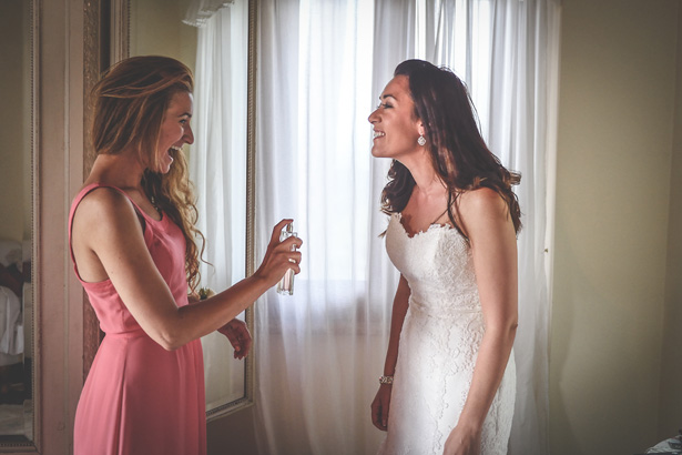 Bridesmaid sprays perfume on the bride | Confetti.co.uk