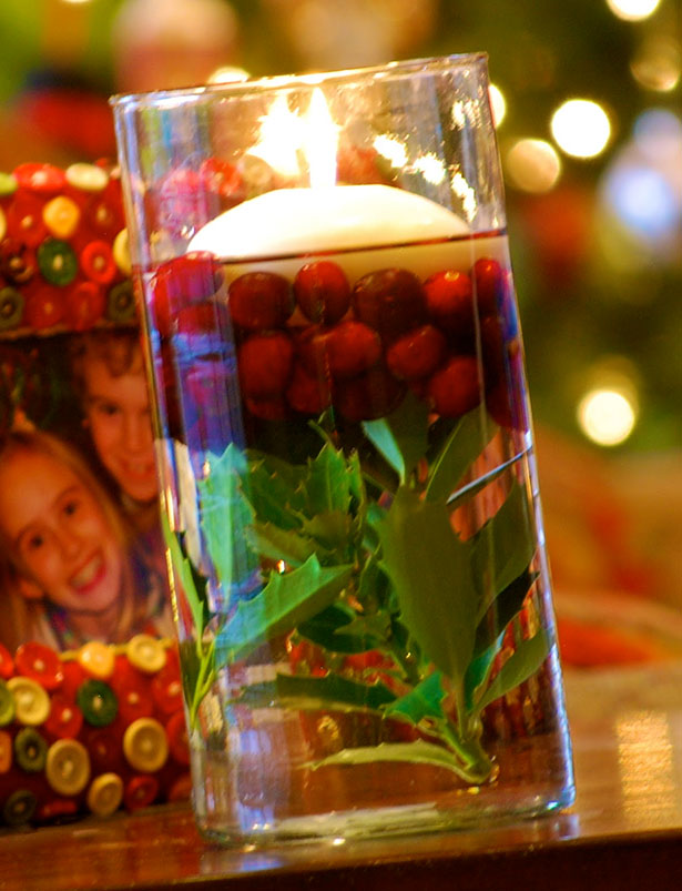 Floating candles in water with cranberries and holly | Christmas table decor| First Christmas as Mr and Mrs | Confetti.co.uk