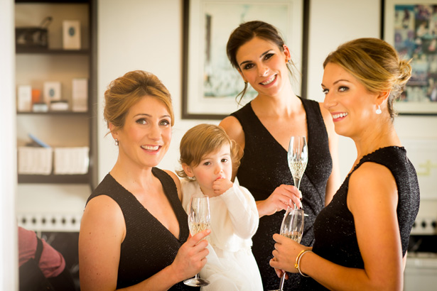 Bridesmaids in black sleeveless dress with the flower girl  | Abigail and Chris's Real Christmas Wedding | Confetti.co.uk