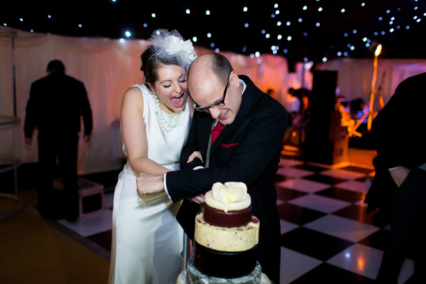Bride and groom cutting their cheese wedding cake| Abigail and Chris's Real Christmas Wedding | Confetti.co.uk