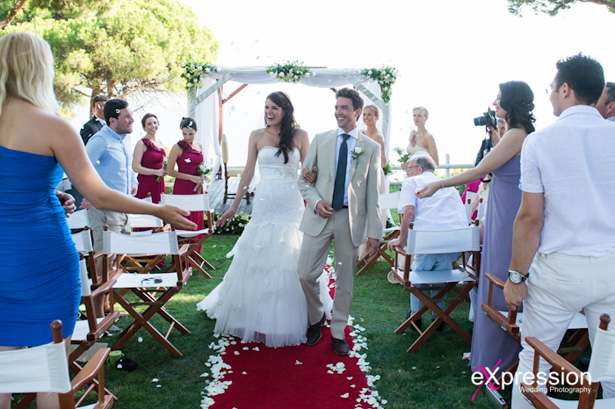 The newlyweds  walking down the aisle as guests celebrate their marriage|Wedding ceremony at the Sheraton Algarve Hotel, in the Algarve, Portugal.| Debora and James's real destination wedding | Confetti.co.uk