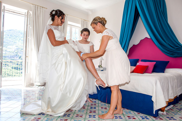 The bridesmaids helping the bride with her garter | Wedding moments you want to capture | Leanne and Chris's Real Italian Wedding | Confetti.co.uk
