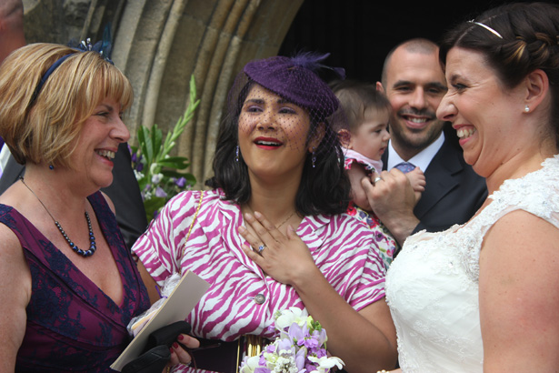Bride having a laugh with her wedding guests | Purple themed wedding| Rhiannon & Michael's Real Wedding | Confetti.co.uk